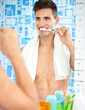 Handsome man brushing teeth