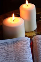 Student studyinhg holy bible by candlelight
