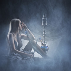 A young blond woman in lingerie smoking a hookah