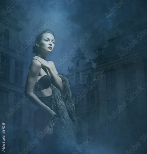 A young woman in a dark dress on a foggy background