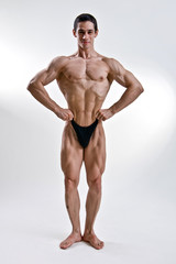 attractive male body builder, demonstrating contest pos