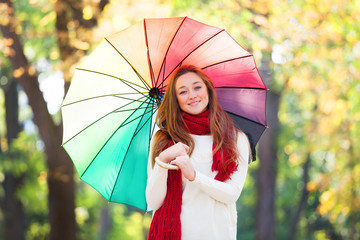 Teen girl in red scarf with umbrella at autumn outdoor