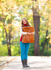 Teen girl with suitcase at autumn outdoor