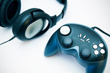 Gamepad and headphones on white background