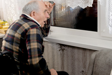 Elderly horrified man watching through a window