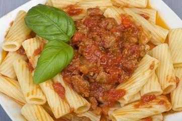 A dish of Maccheroni pasta with tomato souce and sausage