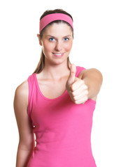 Laughing sporty woman showing thumb