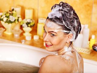 Woman washing hair in bath.