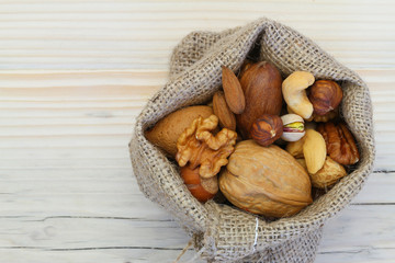 Selection of nuts in jute bag on wooden surface with copy space