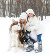 Mother with daughter with huskies dog