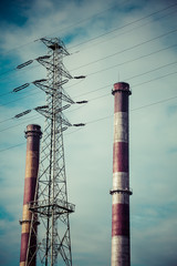 Two industrial chimneys and and a high-voltage electric pylon