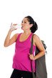 Fit Hispanic pregnant woman drinking water with yoga mat