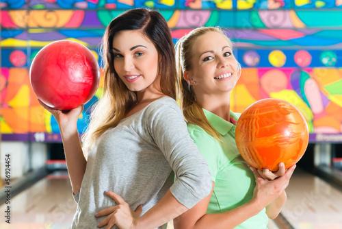 Young women playing bowling and having fun