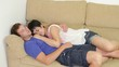 Young happy lovers sleeping on sofa