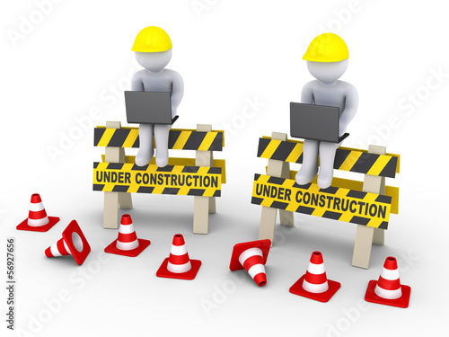 Under construction signs and two workers with laptops