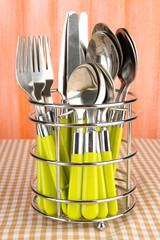 Knives, forks and spoons in metal stand