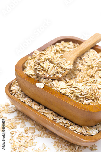 Oat flakes in wooden bowls, isolated on white