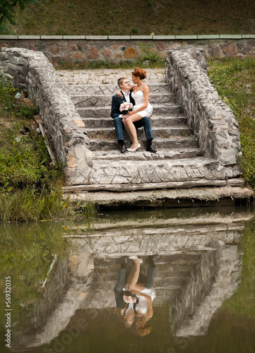 Beautiful newly married couple sitting on stairs near lake