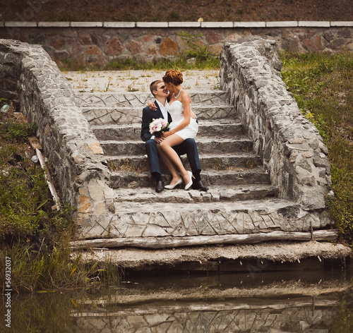 Toned photo of newly married couple sitting on pier