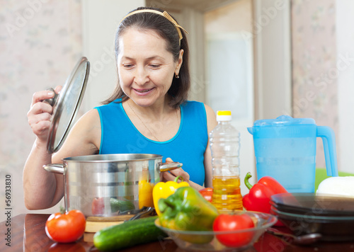mature woman cooking with vegetables