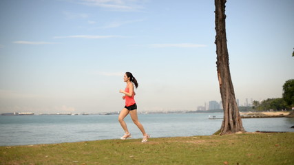 Panning view of Asian Chinese lady jogging by the sea