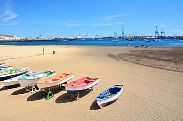Beach with old boats and big port at Las Palmas, Gran Canaria.