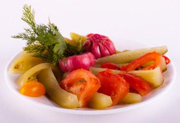 огурцы, помидоры, чеснок и зелень на тарелке
