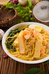 Prawn Laksa soup with rice noodles, shrimps garnished with fresh