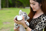 women feeding baby white bengal tiger