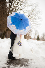 The bride and groom in the park in winter