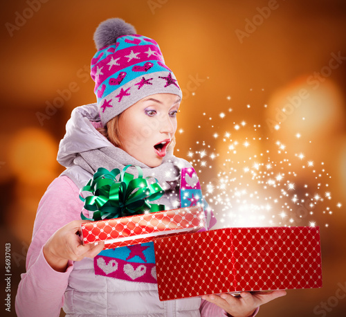 Woman looks into the christmas box  with magic lights