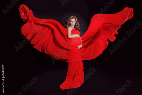 Beautiful Pregnant woman with red blowing tissue isolated on bla