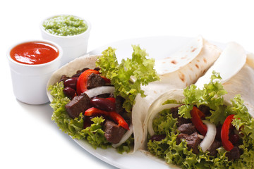 Two burritos with meat and vegetables and sauce isolated