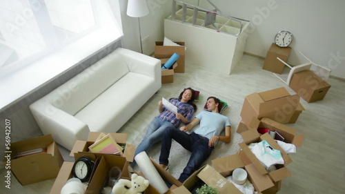 young couple lying among unpacked boxes