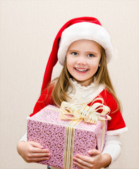 Happy smiling little girl with christmas present