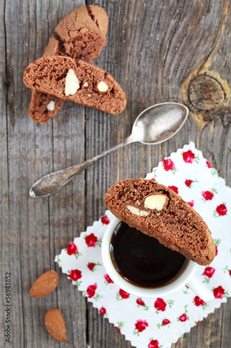 Chocolate biscotti with almonds and cup of coffee on a wooden ta