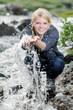 junge blonde Frau beim Wandern erfrischt sich am einem Bach