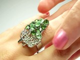 jewelery ring with green emerald crystals purring on the finger