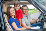 Family with one kid is travelling by car, smiling and looking at