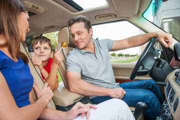 Parents looking at the kid, sitting in a car and smiling