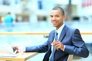 Young african manager sitting at desk in bright office,