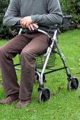 gehbehinderter Mann sitzt in seinem Rollator