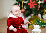 pretty child sitting in front of Christmas tree at home