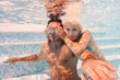 Underwater couple having fun in swimming pool.