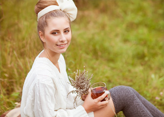 girl drinks tea in retro clothes, enjoying autumn day