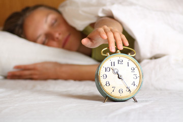 Young sleeping woman and alarm clock in bed