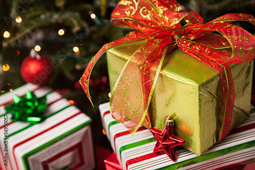 Stack of wrapped Christmas presents under a tree
