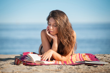 Beautiful young woman reading a book at the beach.