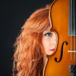 Young woman with violin against black background.