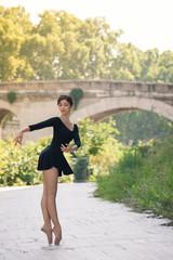 Young beautiful ballerina dancing in Tevere riverside in Rome, I